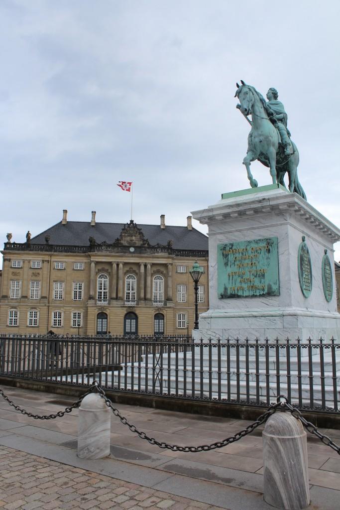 Amalienborg Slotsplads. Udsigt mod Brockdorffs Palæ, som stod færdigbygget i 1760. Her bor kronpris Frederik og Kronprincesse Mary med deres 4 børn. I forgrunden rytterstatue i bronze af Kong Frederik den 5 udført af Jacquues-Francois-Joseph Saly (1717-76) og opstllet på slotspladsen i 1768. Foto den 5. maj 2015 af Erik K Abrahamsen