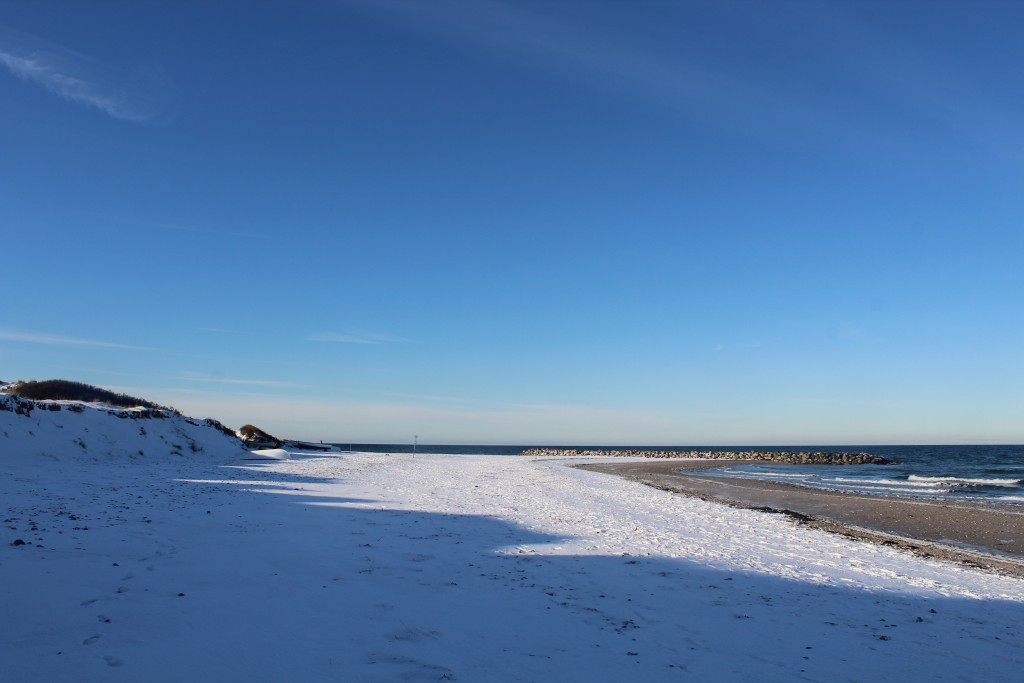 """Liseleje beach. View to """"Pynten"""" with breakwater of big granite stones to protect the historical landing areal for commecial fishing boats established late 1700."""
