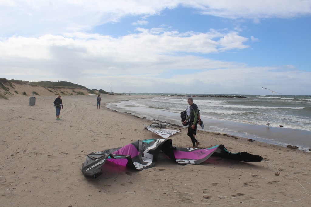 Liseleje beach. A kitesurfer takes a break on the beach before he change his sail to a small sa
