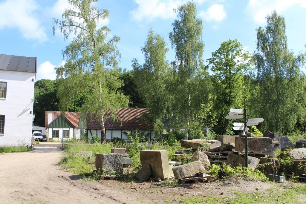 Stenhuggeri som nabo til Raadvad Naturskole som ses i baggrunden af foto.