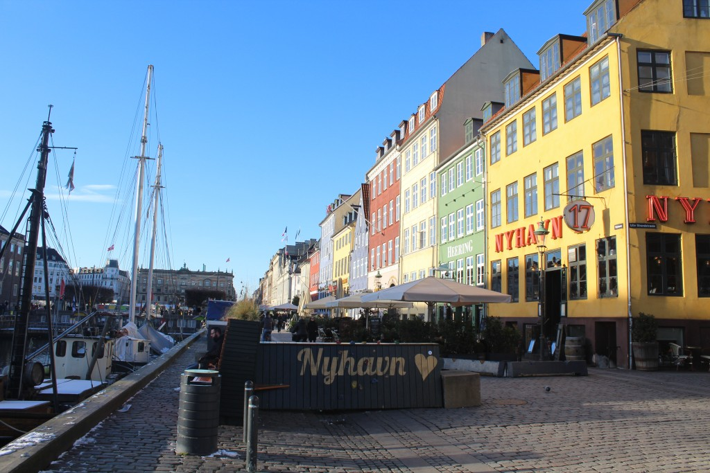 Nyhavn sunny side with outdoor restaurants in former store houses close to wharf. View to concrete barrier covered with bench, floerrs and climbing for children