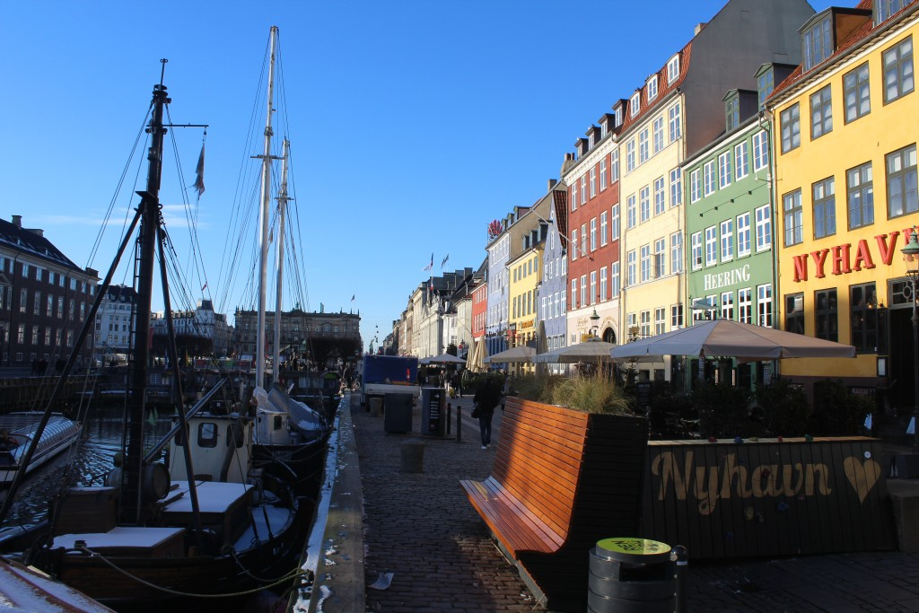 Nyhavn sunny side. View to safety concrete barrier covered with a batch, flowers and a climbing wall for children.
