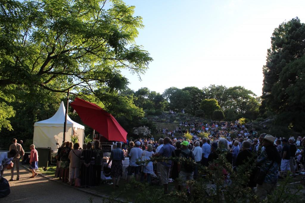 Udsigt mod scene 11 og publikum foran scenen og på skråningen op til Stenhøjen med alpeplanter. Foto den 5. juni 2018 kl 19.30-50 af Erik K Abrahamsen.