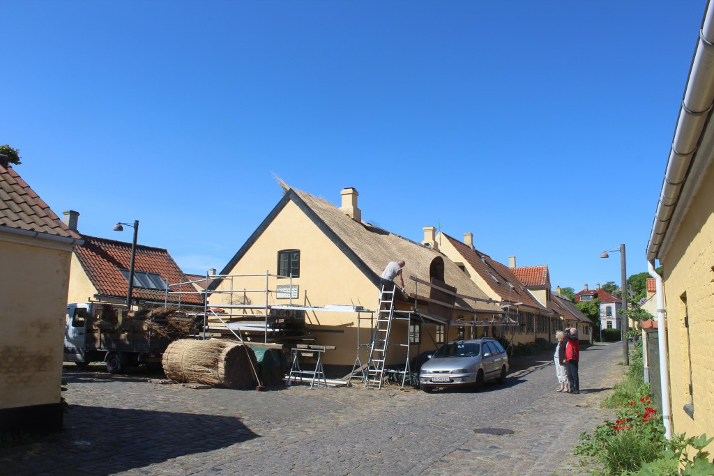 A thatcher renews a thatched roof in Dragoper Old Fishing Village.