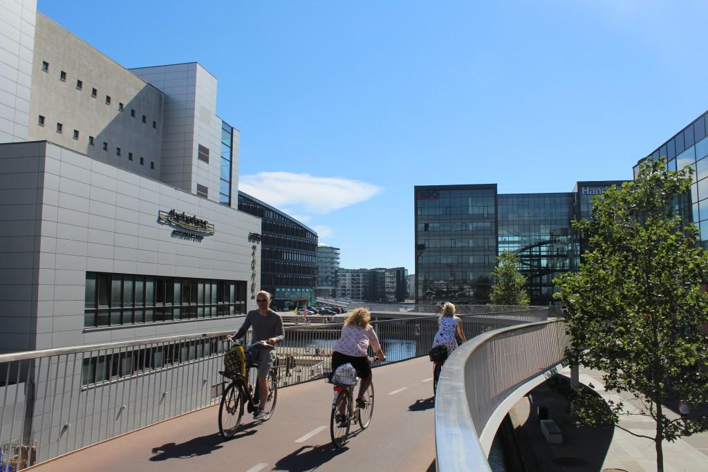 "The Bicycle Snake at Fisketorvet Shopping Center at kalvebod Brygge. View in direction south to Havneholmen and bridge ""Bryggebroen"" 25. august 2016 by Erik K Abrahamsen."
