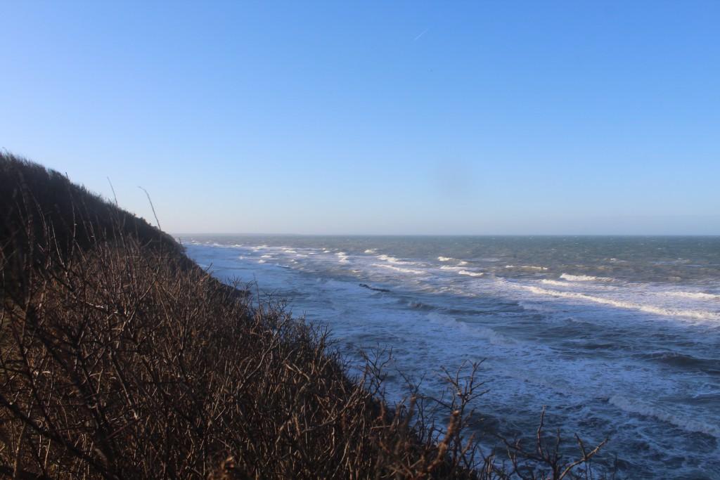 Hyllingebejrg Strand. Udsigt mod vest mod 2 bølgebrydere af granitsten ca 75 m ud for skrænten.