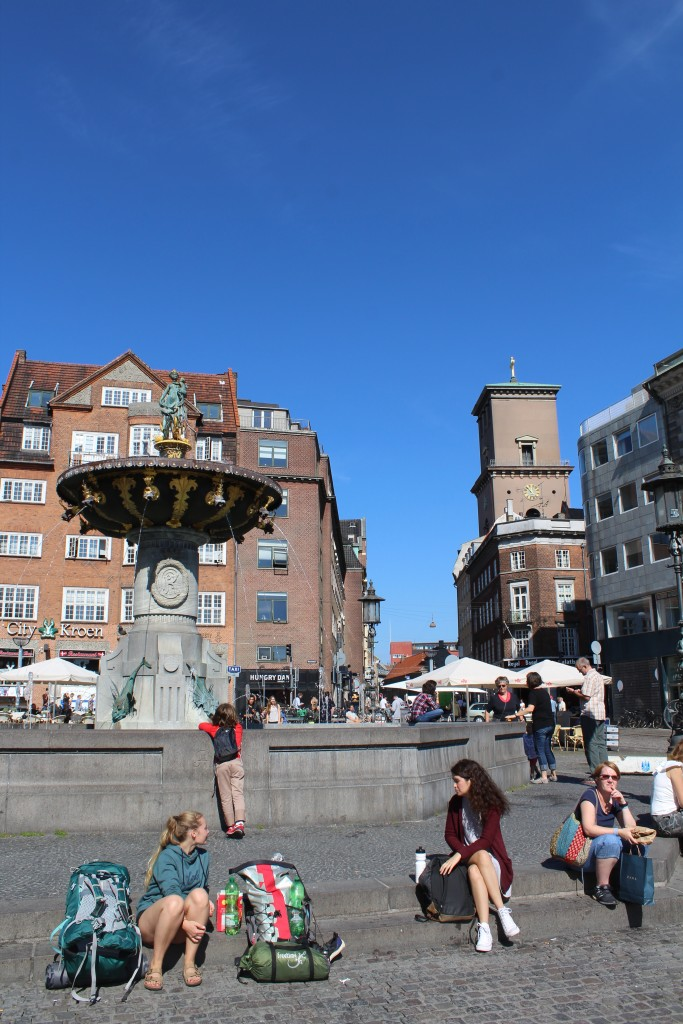 """Old Square, Gammel Torv - main square since the offiv´cial foundation of Copemhaen in 1167 by Bishop Absalon. View to Fouantain """"Caritas"""" v´built 1608 and to Chathedarl of Copenhafen """"Vor Frue Kirke"""" built 1811-31 in style greek-roman by Architect C. F . Hansen."""