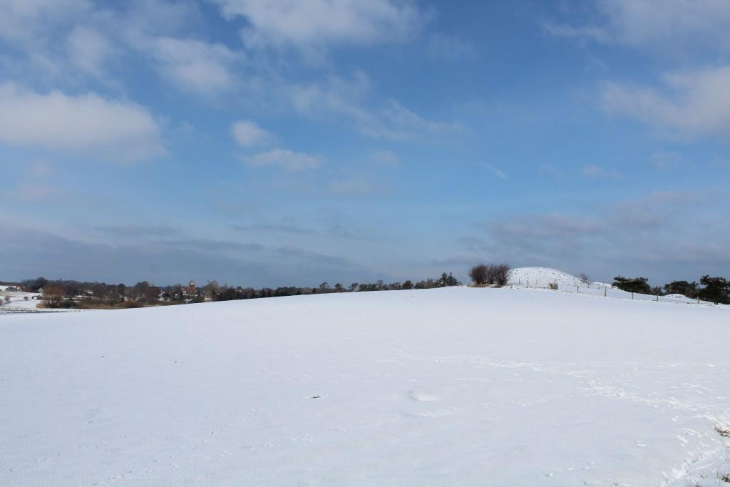 Melby. Udsigt mod Melby med Melby Kirke og Melby Mølle og mee bronzealder gravhøj til højre i billedet. Foto den 10. marts 2018 af Erik K Abrahamsen.